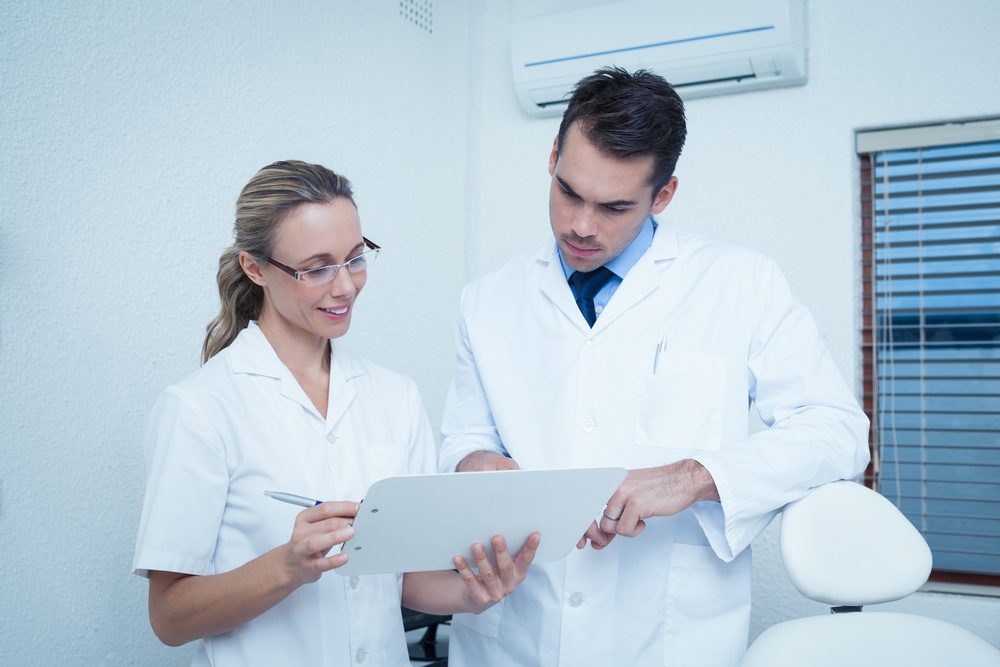 ZA_027_View of female and male dentists discussing reports.jpeg